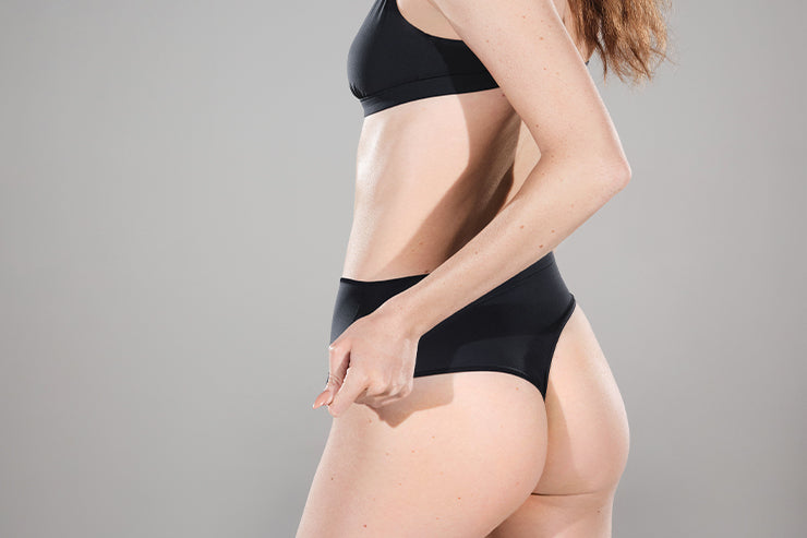A model shot from behind shows the SKIMS Fits Everybody Thong in Onyx