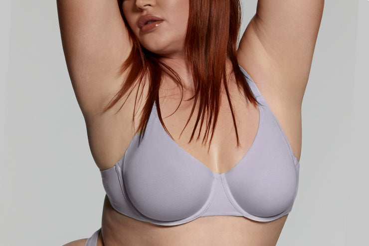 A model lifts her arms wearing her SKIMS underwire bra.
