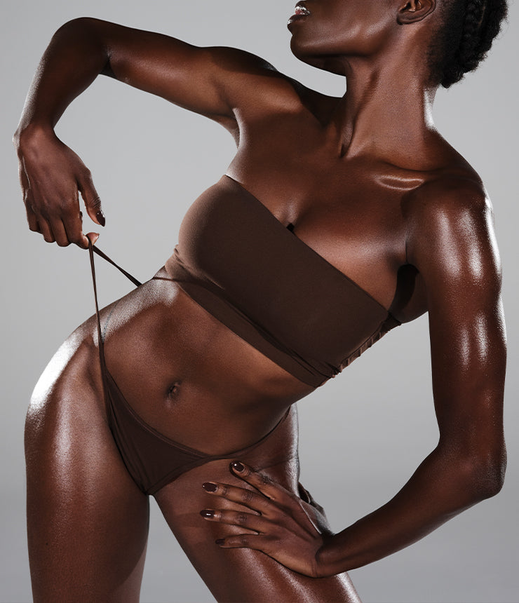 A model pulls on the hip string of her SKIMS Fits Everybody T-String Thong in Cocoa