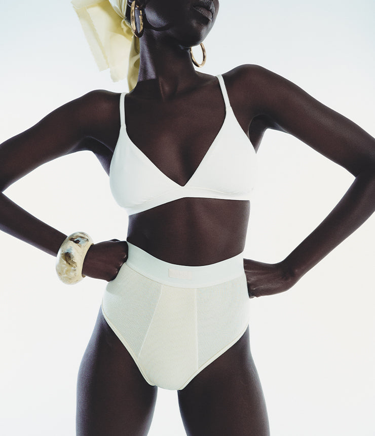 A SKIMS Model poses in Cotton Rib High Waisted Briefs in Bone