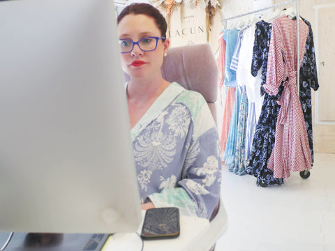 Photo of House of Lacuna founder and creative director Naomi Swalwell working at her computer in her studio.