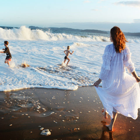 Photo of House of Lacuna founder and creative director Naomi Swalwell at the beach with her two children.