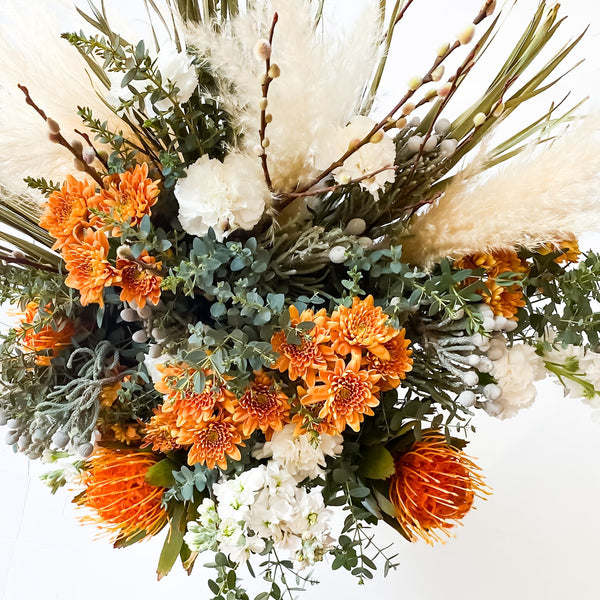 The Lucy Bouquet includes 30+ stems of:  Pincushions, Pavafolia, Dried Pampus, Carnartions, Brunia, Pussy Willow, Dried Palm Leaves, Foliage Spray.