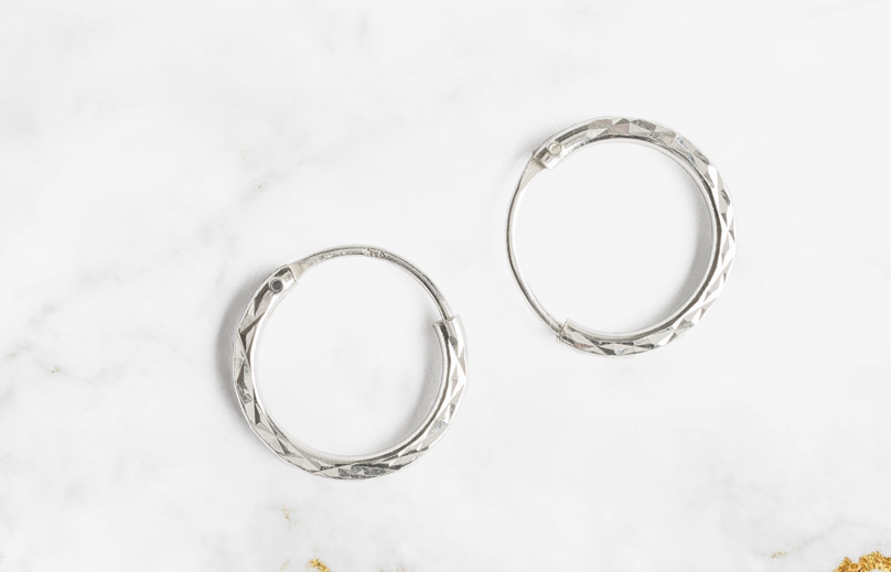 Show your feminine side with these sterling silver diamond cut hoop earrings. Striking, classic, and elegant, these hypoallergenic sterling silver earrings are a great accessory for a relaxing day in or a night out.