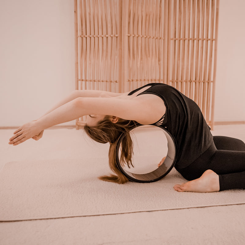 Young woman doing a back-stretch asana with Yogibato Yoga wheel