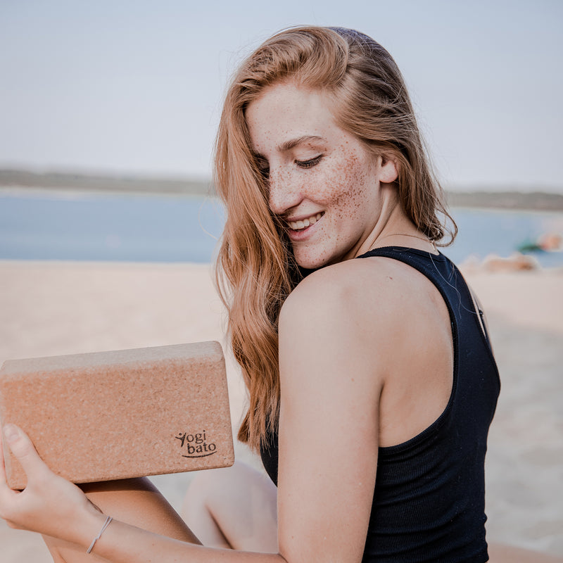 Yogi at the beach of Portugal looking at one Yogibato yoga brick made of cork