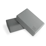 Bundle of two grey Yogibato Yoga Blocks made of EVA foam lying on top of each other showing non-slip material and flattened edges