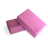Bundle of two fuchsia Yogibato Yoga Blocks made of EVA foam lying on top of each other showing non-slip material and flattened edges