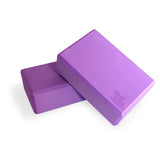 Bundle of two purple Yogibato Yoga Blocks made of EVA foam lying on top of each other showing non-slip material and flattened edges