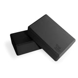 Bundle of two black Yogibato Yoga Blocks made of EVA foam lying on top of each other showing non-slip material and flattened edges