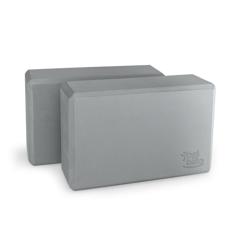 Set of two grey Yogibato Yoga Blocks made of EVA foam standing behind each other showing non-slip material and flattened edges