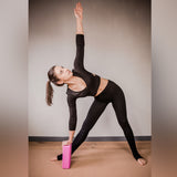 Yogi practicing yoga using grey Yogibato yoga block as stretching aid and support
