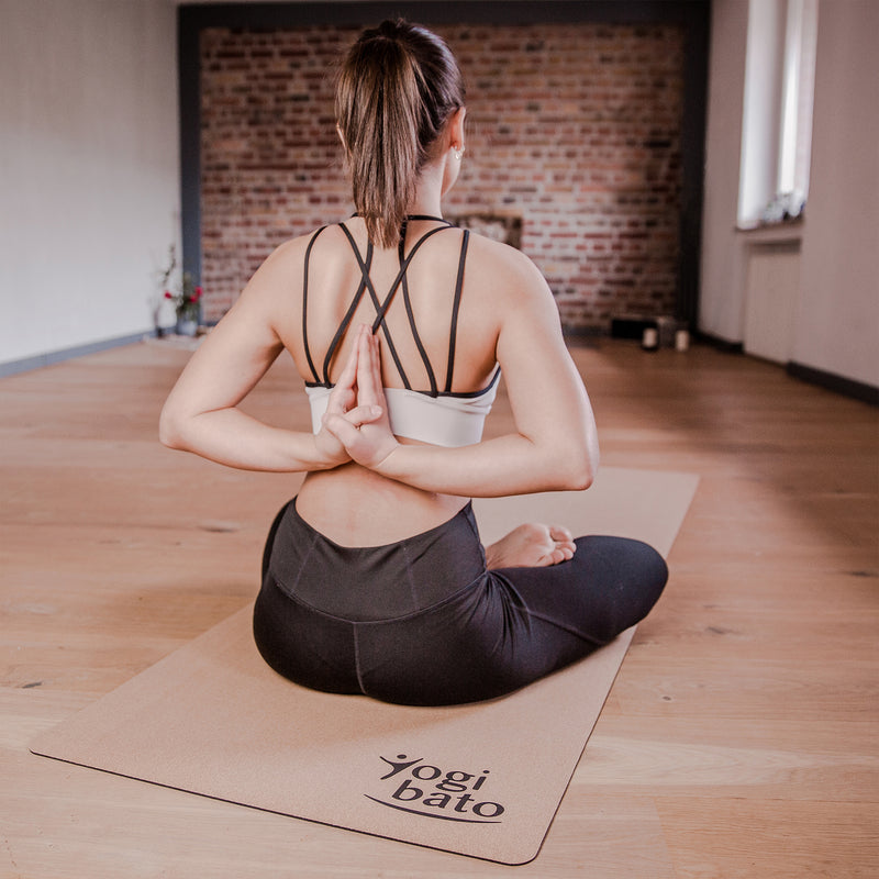Yogi practicing yoga with hands behind the back on a Yogibato yoga mat made from cork and rubber