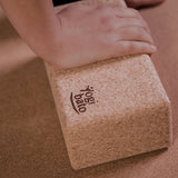 Hand of yogi on Yogibato yoga cork block while practicing yoga