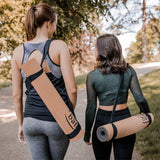 Two yogis after yoga practice carrying their yoga mats with Yogibato carrying strap in natural cotton