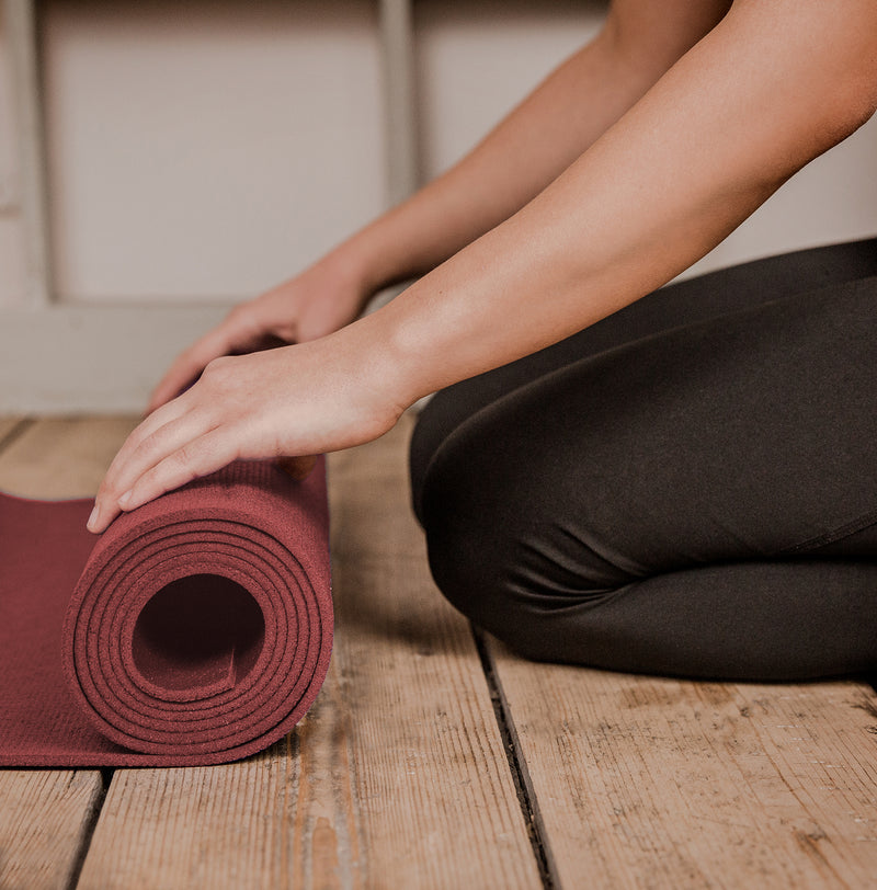 Girl rolling up Yogibato yoga mat studio after practice showing anti-slip surface of sports mat Bordeaux