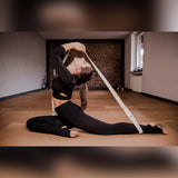 Woman sits on a yoga mat with her back stretched out uses a yogibato yoga belt to help