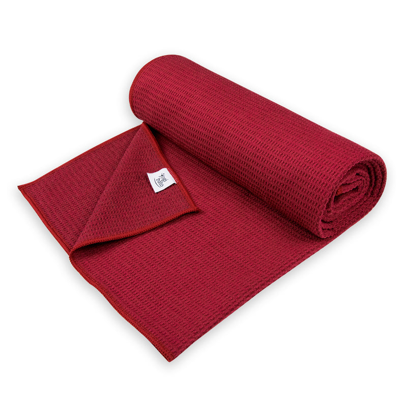 Semi-rolled Yogibato Yoga towel in bordeaux with textile label