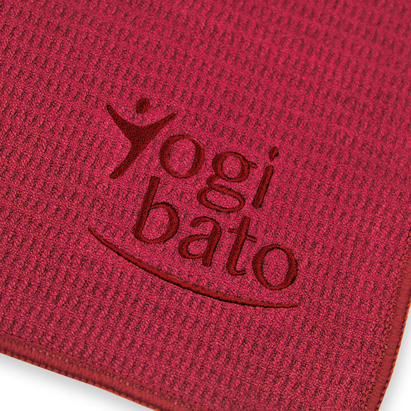 Detailed view of the top side of a yoga towel in bordeaux with embroidered Yogibato logo