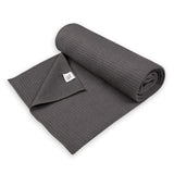 Semi-rolled Yogibato Yoga towel in dark-grey with textile label