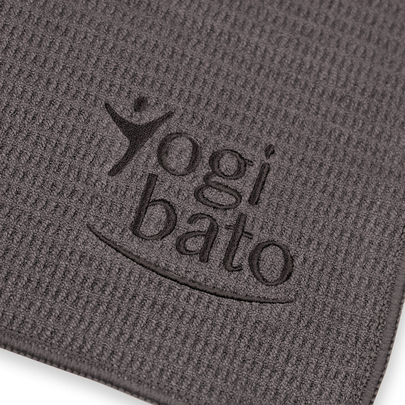 Detailed view of the top side of a yoga towel in dark-grey with embroidered Yogibato logo