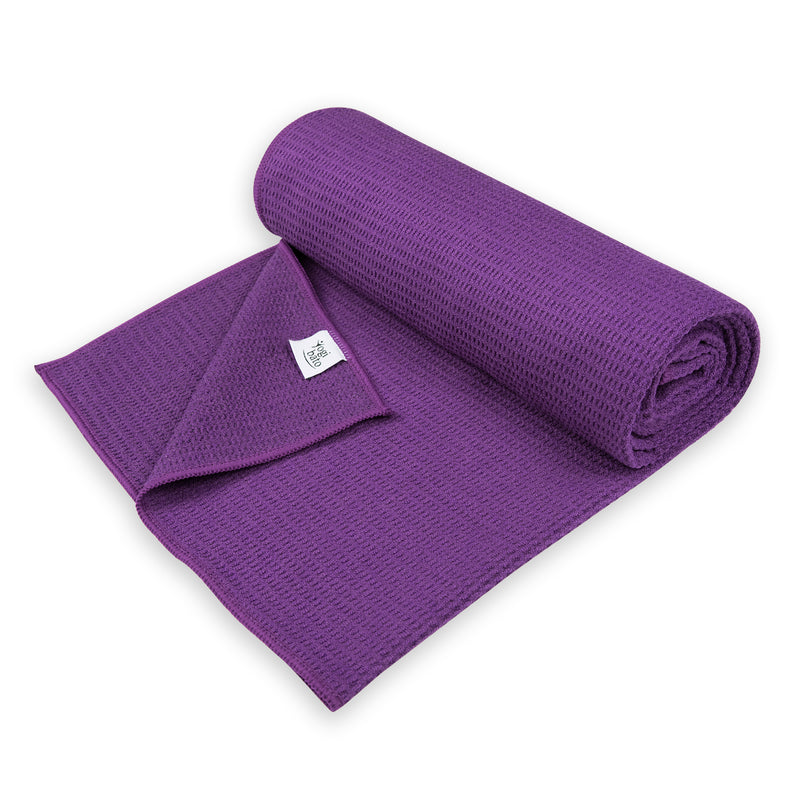 Semi-rolled Yogibato Yoga towel in purple with textile label