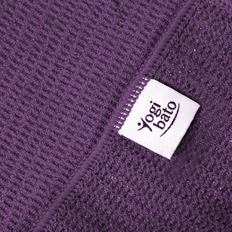 Detailed view of the upper side of a yoga towel in purple and the silicone-coated underside with textile label