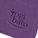 Detailed view of the top side of a yoga towel in purple with embroidered Yogibato logo