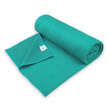 Semi-rolled Yogibato Yoga towel in turquoise with textile label