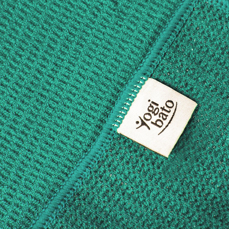 Detailed view of the upper side of a yoga towel in turquoise and the silicone-coated underside with textile label