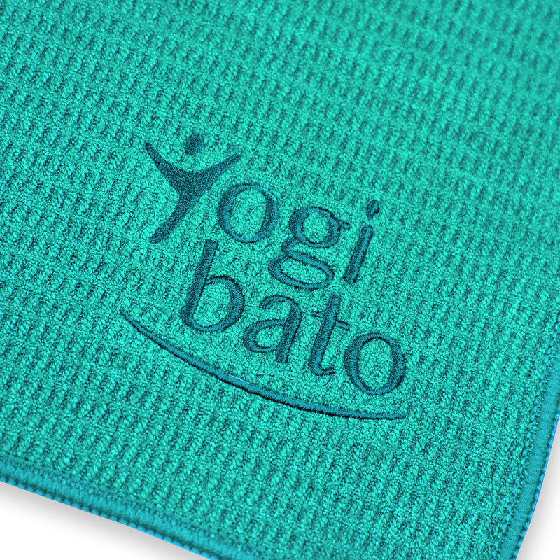 Detailed view of the top side of a yoga towel in turquoise with embroidered Yogibato logo