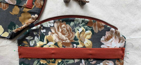 a close up image of the interior of a pouch featuring floral fabric and a rust coloured knit band