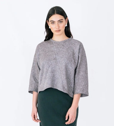 A white woman with long dark hair, she is standing in front of a white background and is wearing a mid grey top. the top has seams going diagonally across it so it can be made of 4 different pieces of fabric. She is wearing it with a dark green skirt.
