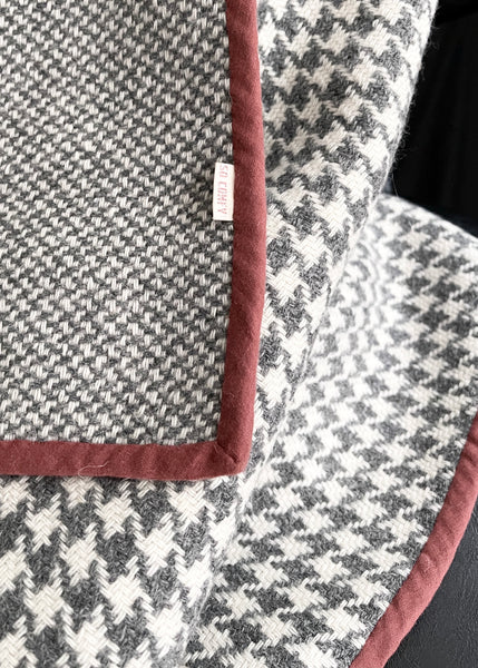 a close up of the so cosy label on the grey and white check blanket that has terracotta binding