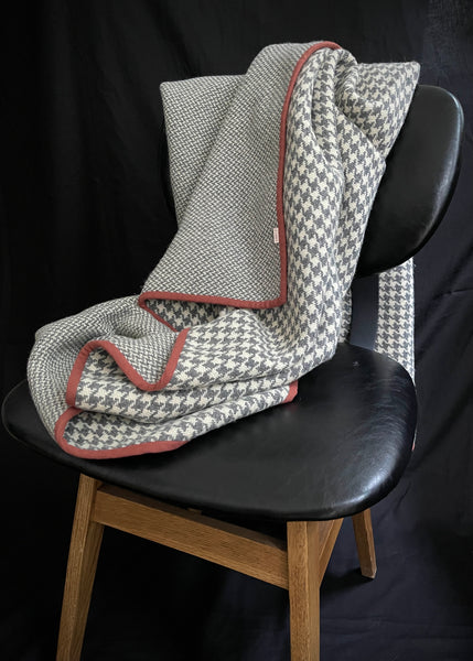 a heavy woollen blanket draped over a chair with a black seat and wooden legs. It has a black background