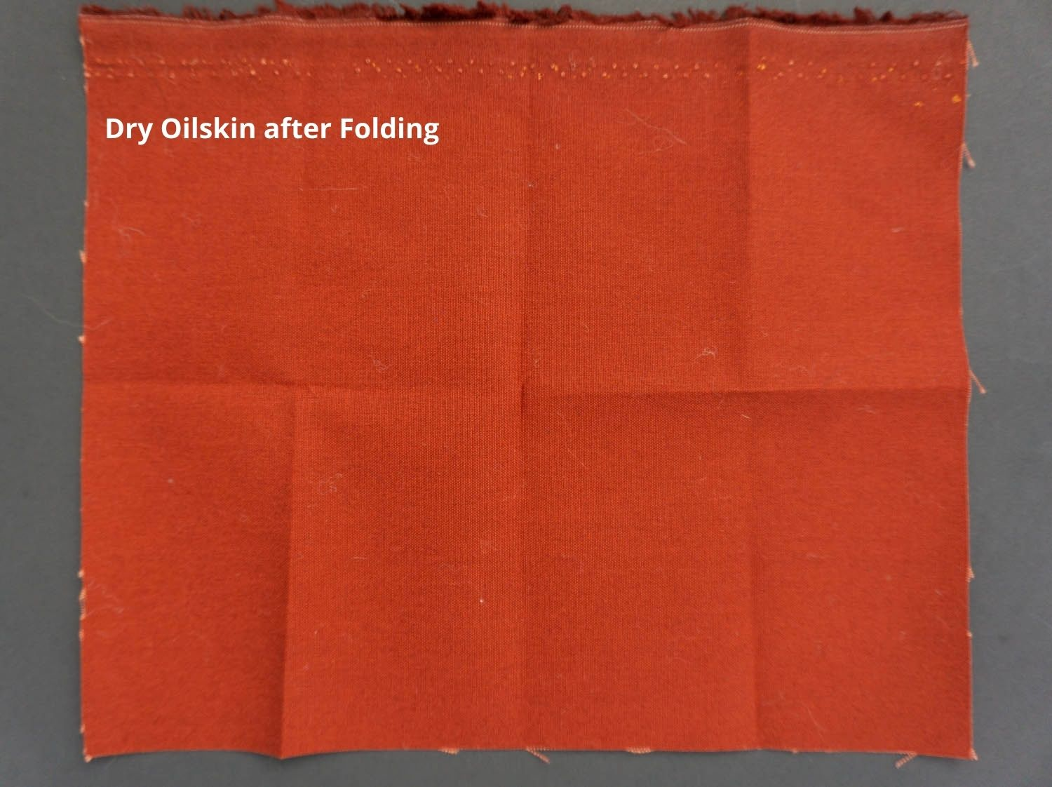 a picture of red oilskin that has been folded and then opened and laid flat on a black background
