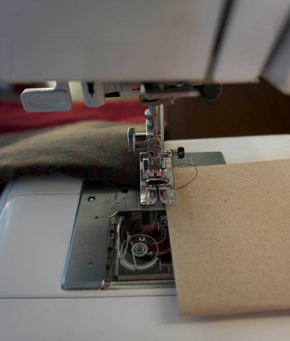 a picture of the front of the machine, close up to the foot. the cardboard is at the side and the fabric at the back.
