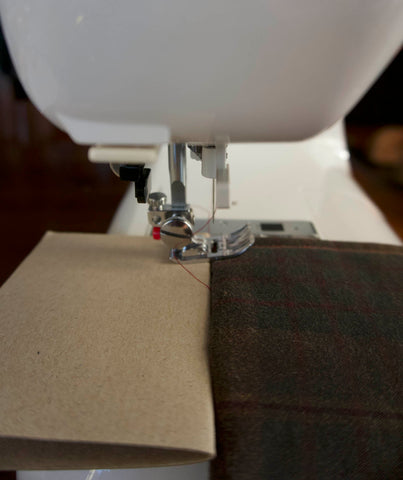 a side view of a sewing machine with a close up of the foot. the back of the sewing foot is lifted up by a wedge of cardboard