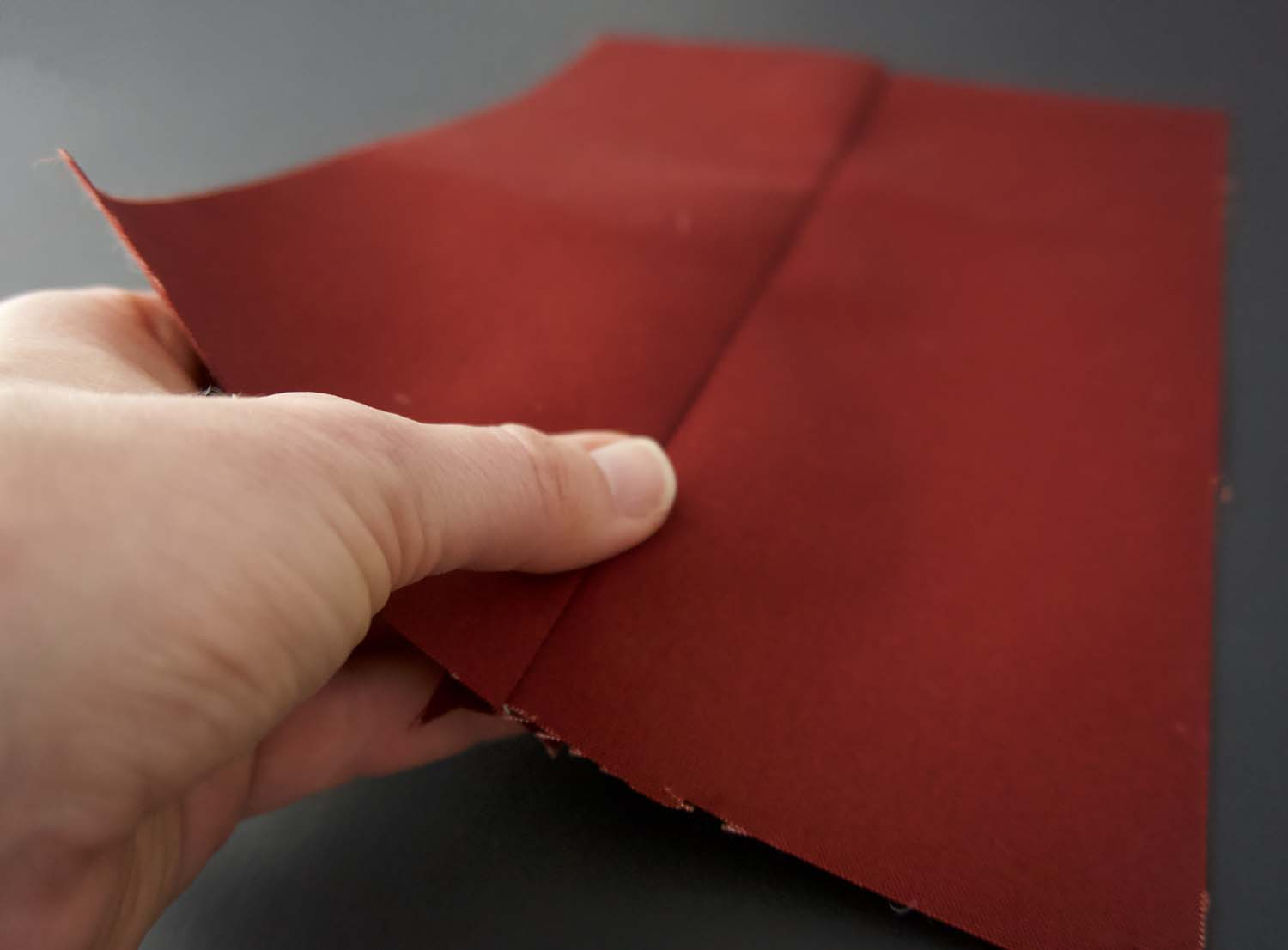 a picture of a thumb pressing down a seam on some dark red oilskin