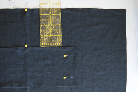 the apron laid out and a long ruler sticking out the pocket