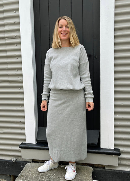 white lady wearing a light grey jumper and matching straight skirt