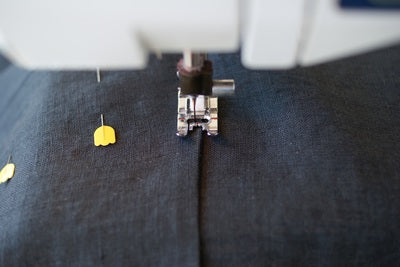 A close up of a sewing machine foot sewing close to the edge of the pocket