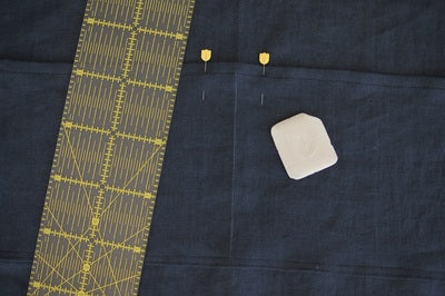 pocket with a ruler and chalk on the denim and a chalk mark down the centre to show the placement of the stitching