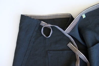 a close up of a dark blue denim apron with a white and blue stripe tie