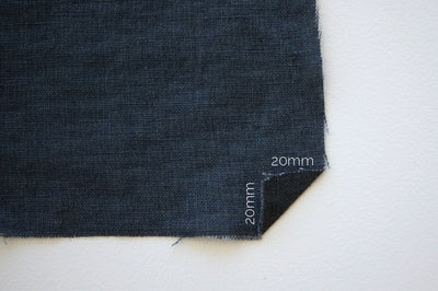 a blue denim square with a small corner folded up and 20mm written on it.