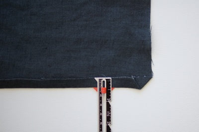 a dark blue denim rectangle with a side folded up and a sewing gauge showing the amount of 1cm