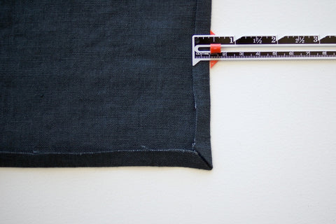 a blue denim square with the side folded up and a sewing measuring gauge showing the distance of 1cm