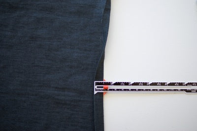 a blue denim square showing the top edge folded over and a measuring gauge showing the amount that it is pressed over by which is 12mm