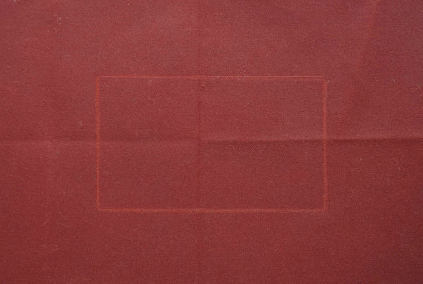 a dark red oilskin which has a white rectangle traced on it.
