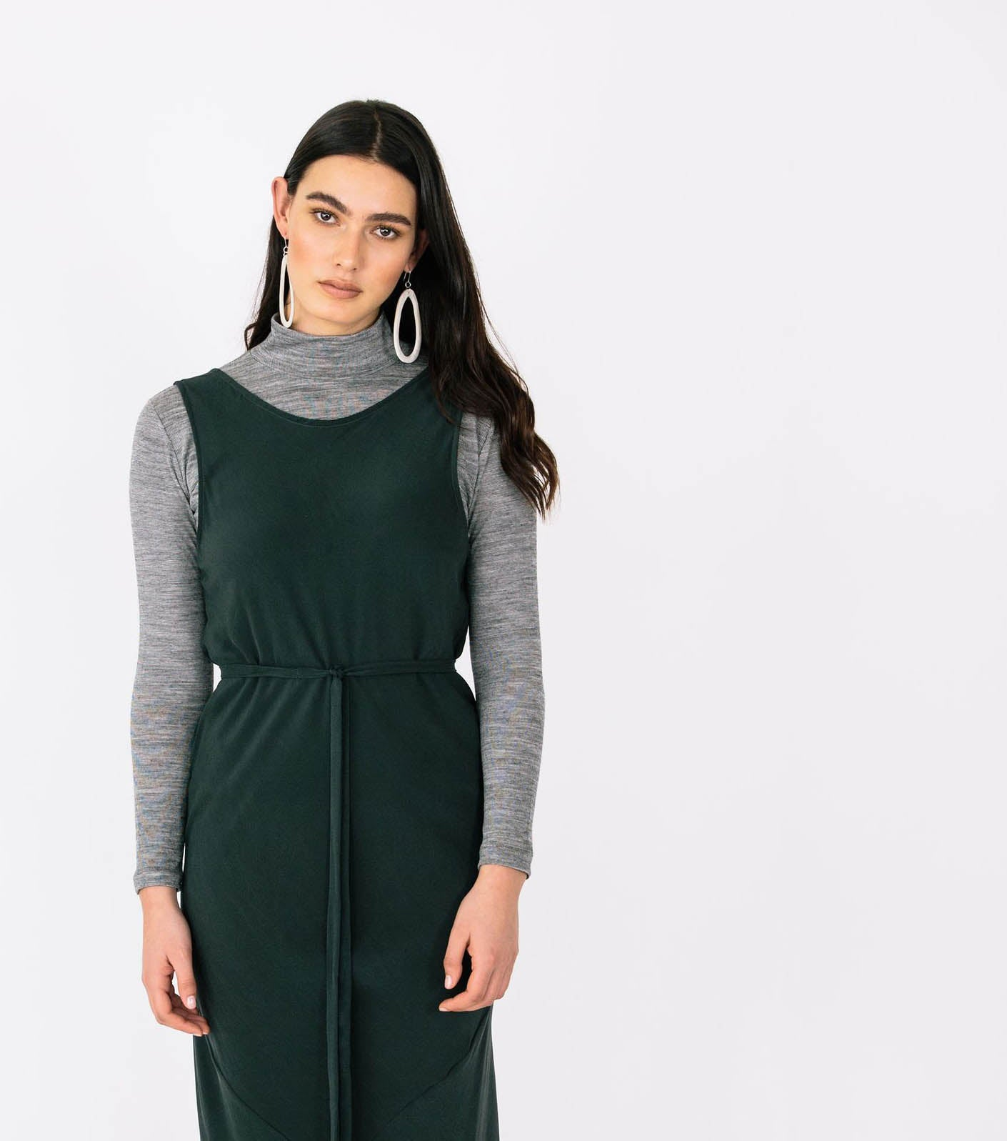 a picture of a white woman with long dark hair wearing a dark green dress layered over the top of a grey turtleneck